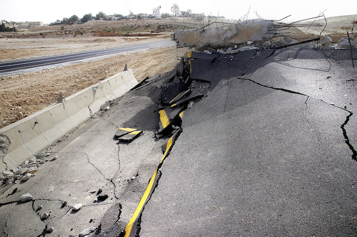 A road buckled and broken by an earthquake. ©iStock