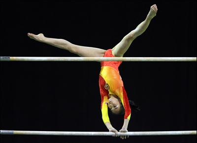 A gymnast swings and twists on the uneven bars