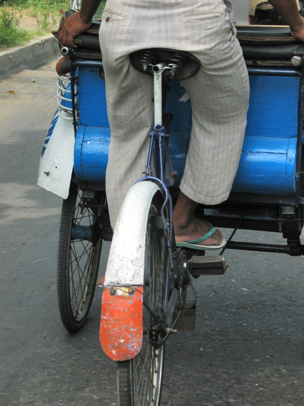 The becak driver pedals his vehicle. Just like pedalling a bicycle!
