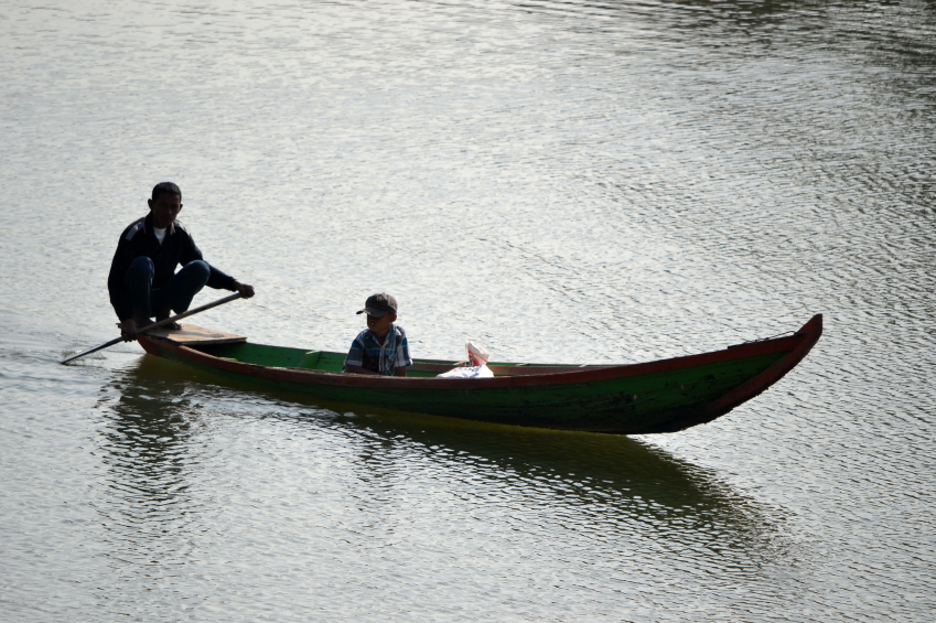 Small boats are used by farmers and families living by a river.