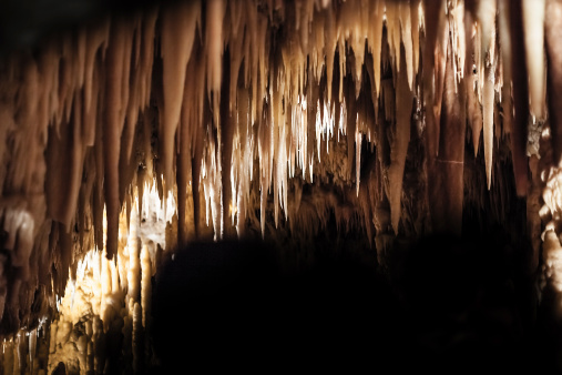 Stalactites hang from the roof of a limestone cave. ©Getty Images