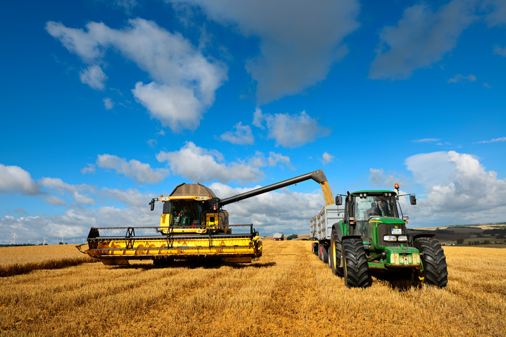A combine harvester unloads grain into a tractor trailer © iStock/Getty Images