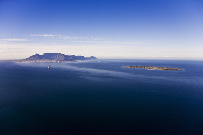 Robben Island (right) is a small, flat island off the coast of Cape Town, South Africa. Cape Town, at the foot of the famous Table Mountain, is on the left. Photo ©iStock