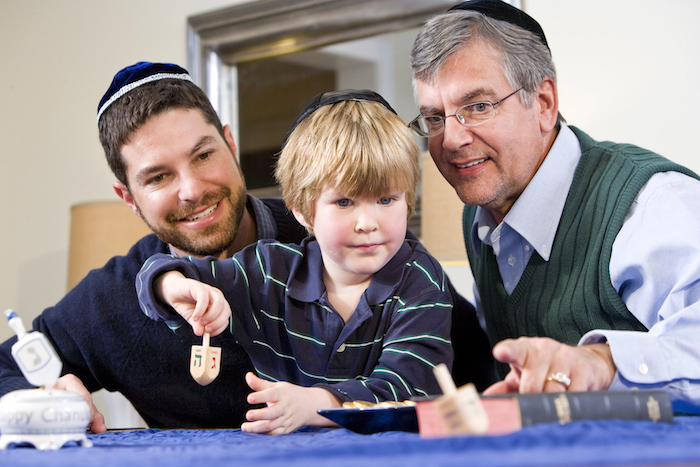 A little boy being taught by his father and grandfather a game played at Hanukkah called 'Spin the Dreidel'. All are wearing a cap called a yamulka.  Photo©iStock