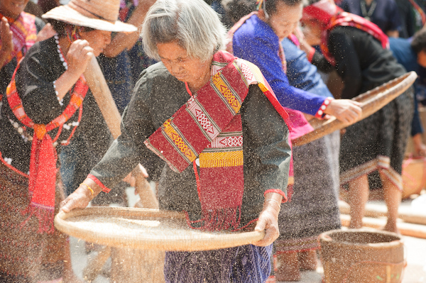Rice grains are tossed into the air to let the husk, or coating, fly away. These women are Thai. Photo©iStock