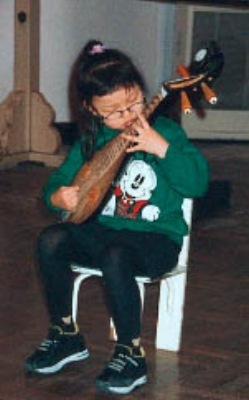 A student learns to play a traditional Chinese musical instrument (kidcyber)