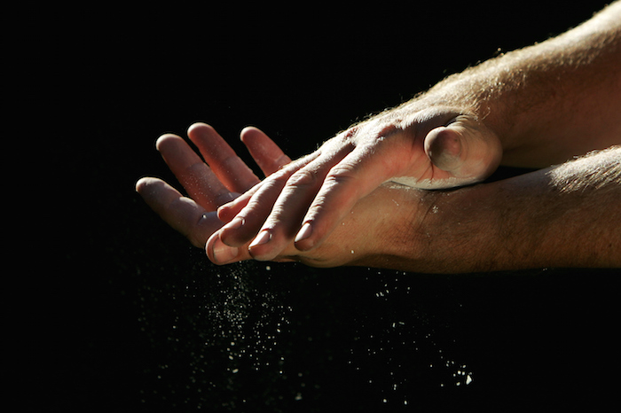 Weightlifters rub their hands with chalk to grip the bar without slipping. ©Getty
