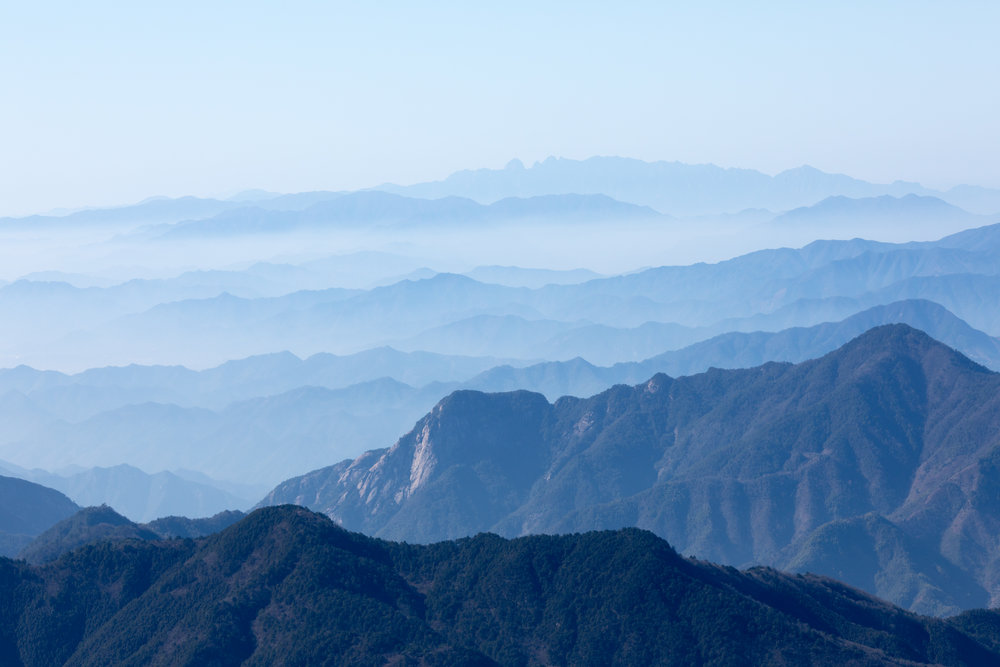 View of Huangshan mountains (center-top) from the summit of Qingliang Feng mountain, China