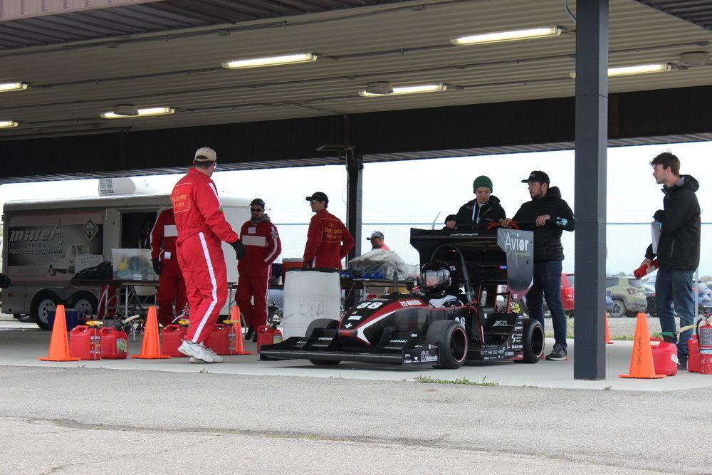 Nous voici à la station de carburant pour faire le plein. Croyez le ou non le moteur de notre voiture roule au jus de blé d'Inde! -- Here we are at the fuel station. Believe it or not, our car runs on corn juice!