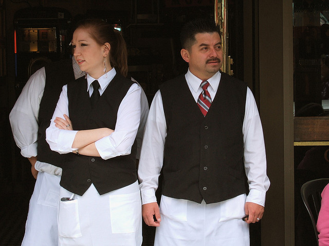 Waiter and waitress wait to help a diner