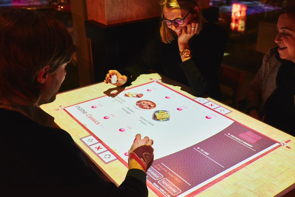 Guests can order food through their interactive menu projected onto their table.