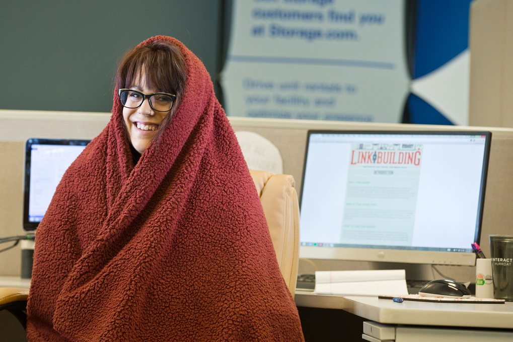 Molly Mahannah wearing a sweatshirt and a blanket at her desk at B2 Interactive, a web design and digital marketing agency, in Omaha, Neb., July 31, 2015. Most office buildings set temperature based on a formula from the '60s based on the metabolic rates of men. This formula is now being challenged to reduce energy consumption and combat global warming. (Chris Machian/The New York Times)