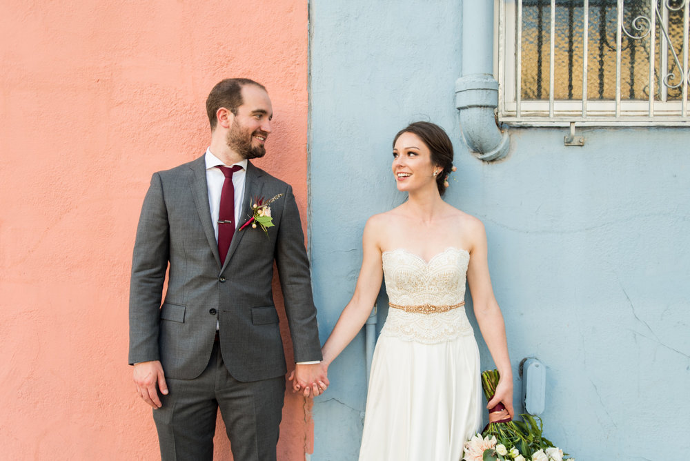 Bride and Groom in front of pink and blue wall in San Francisco
