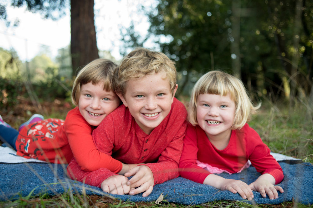 Three siblings laying down during holiday photo session