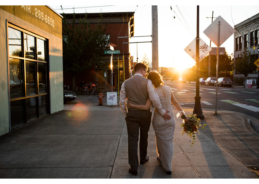 Golden hour portrait of bride and groom walking down street in North Portland
