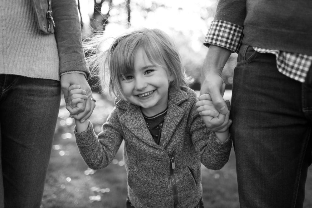 Black and white photo of girl holding parents hands in Portland