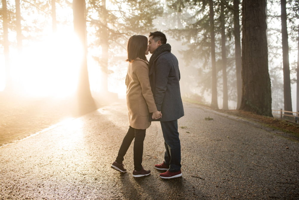 Couple kissing in dramatic sunlight and fog at Mt Tabor