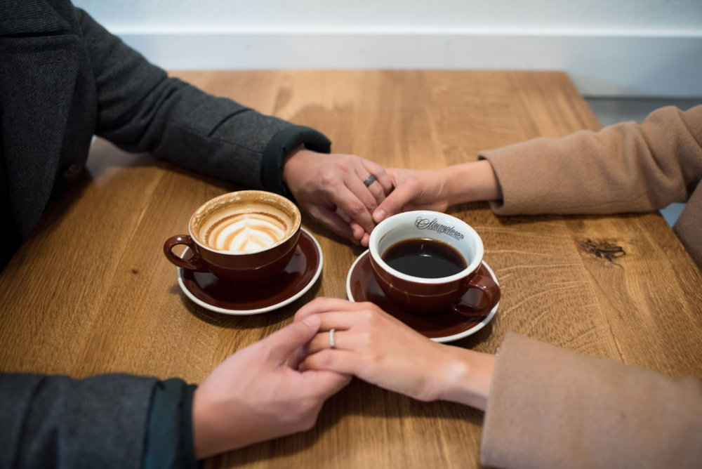 Detail photo of couple holding hands with coffee cups
