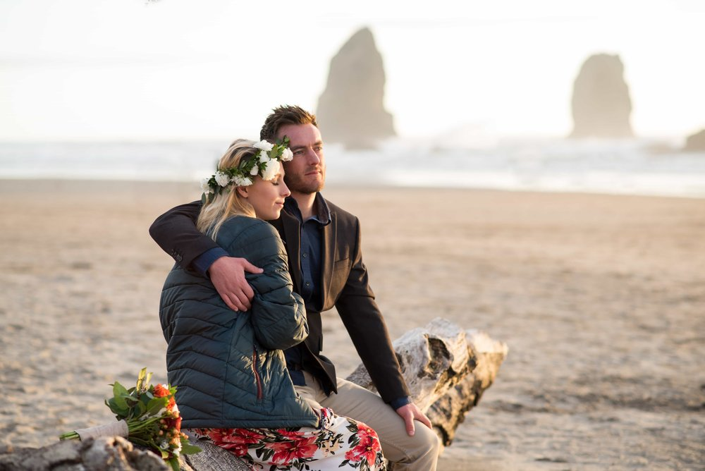 Bride and Groom snuggling driftwood log at Cannon Beach