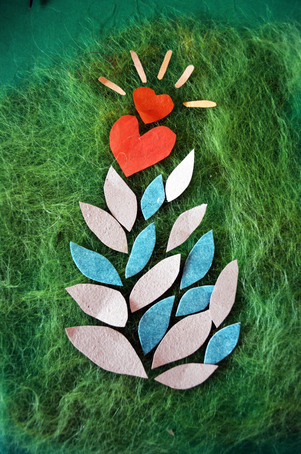 Natalya Garden-Thompson,  Creative Vitality                                                                                 Photograph of a collage made from:  light brown  handmade paper & green etchings on paper shaped as leaves; orange paper   love hearts with yellow  radiating lines on top. All laying on top of green silk paper.   © all images by   Natalya Garden-Thompson, 2016