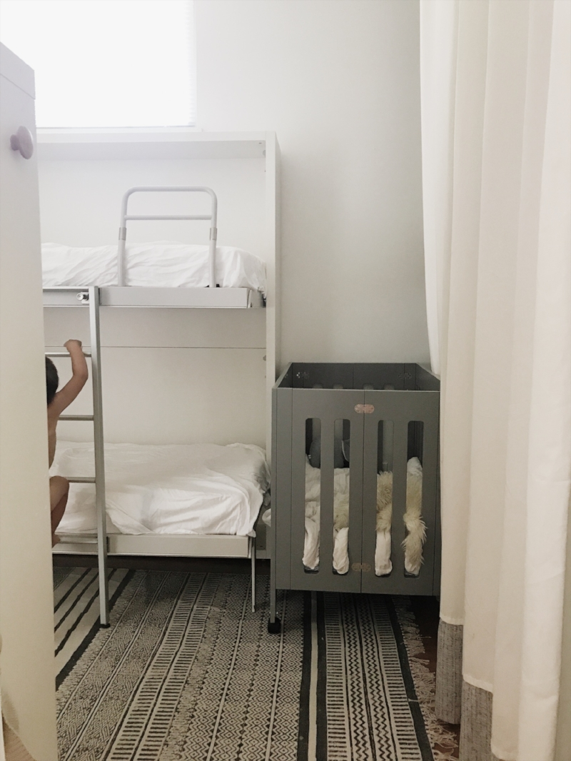 The mini crib back in our space tucked beside our master closet and the wall beds.  Closet doors were removed long ago and replaced with curtains.
