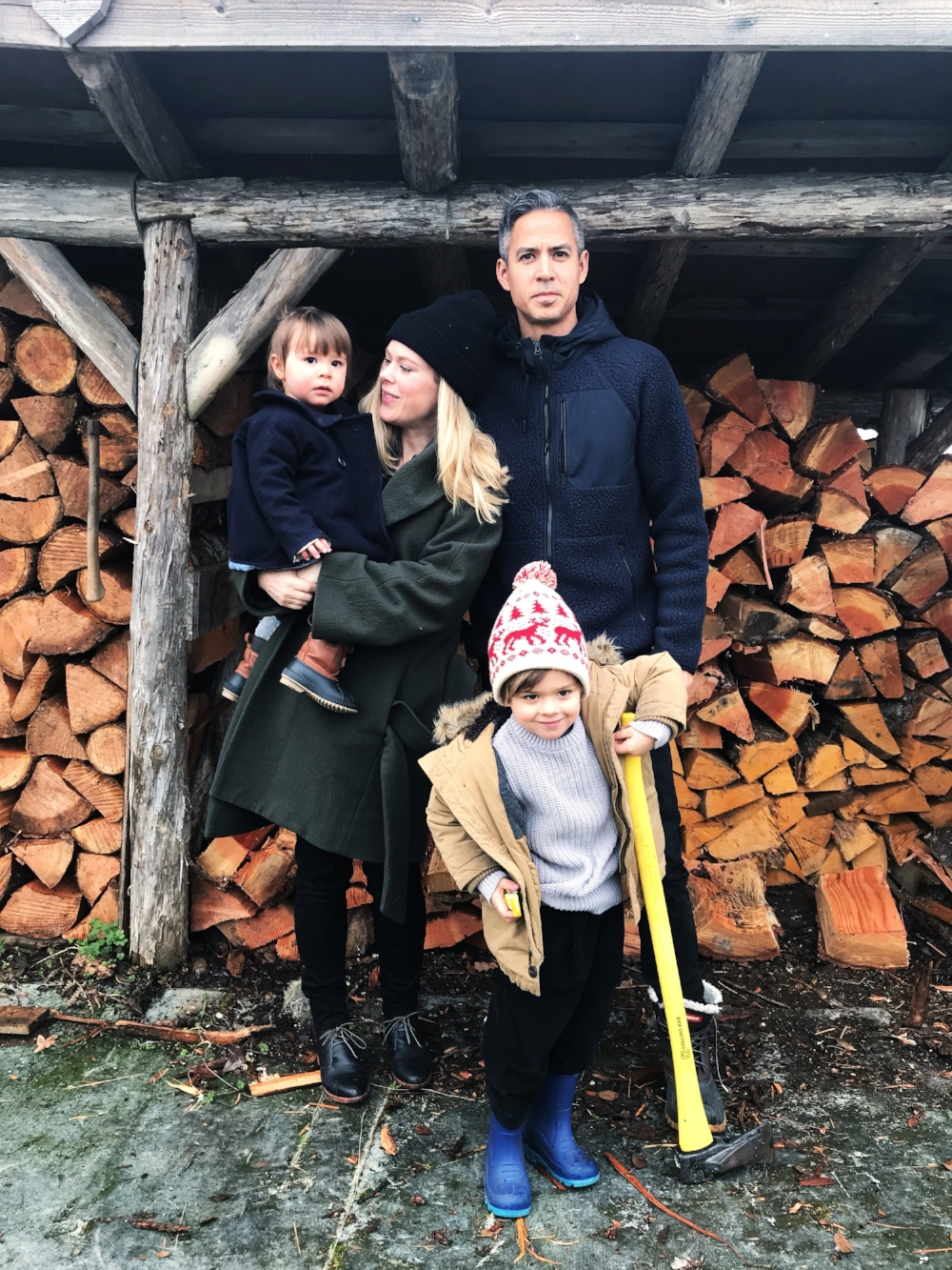 family photo-op in front of the wood pile