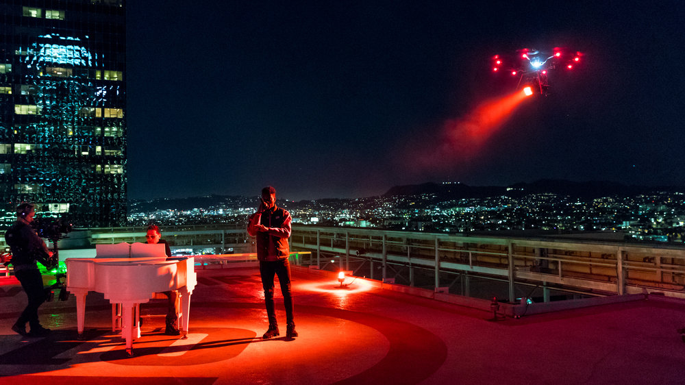 A drone lights up the helipad for Thutmose (vocals) and Storch (piano). A steadicam moves in to capture the magic of the moment. Photo Credit:Jeffrey Moustache