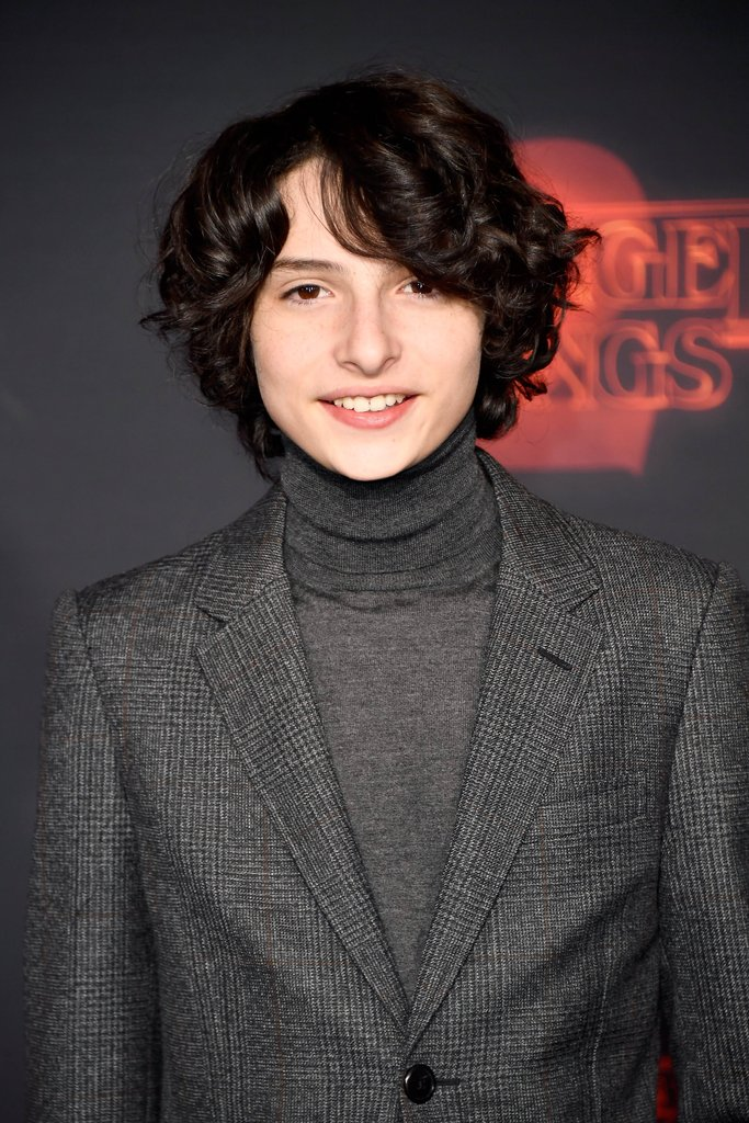 [Image Description: Finn Wolfhard smiling for the camera at the red carpet.]