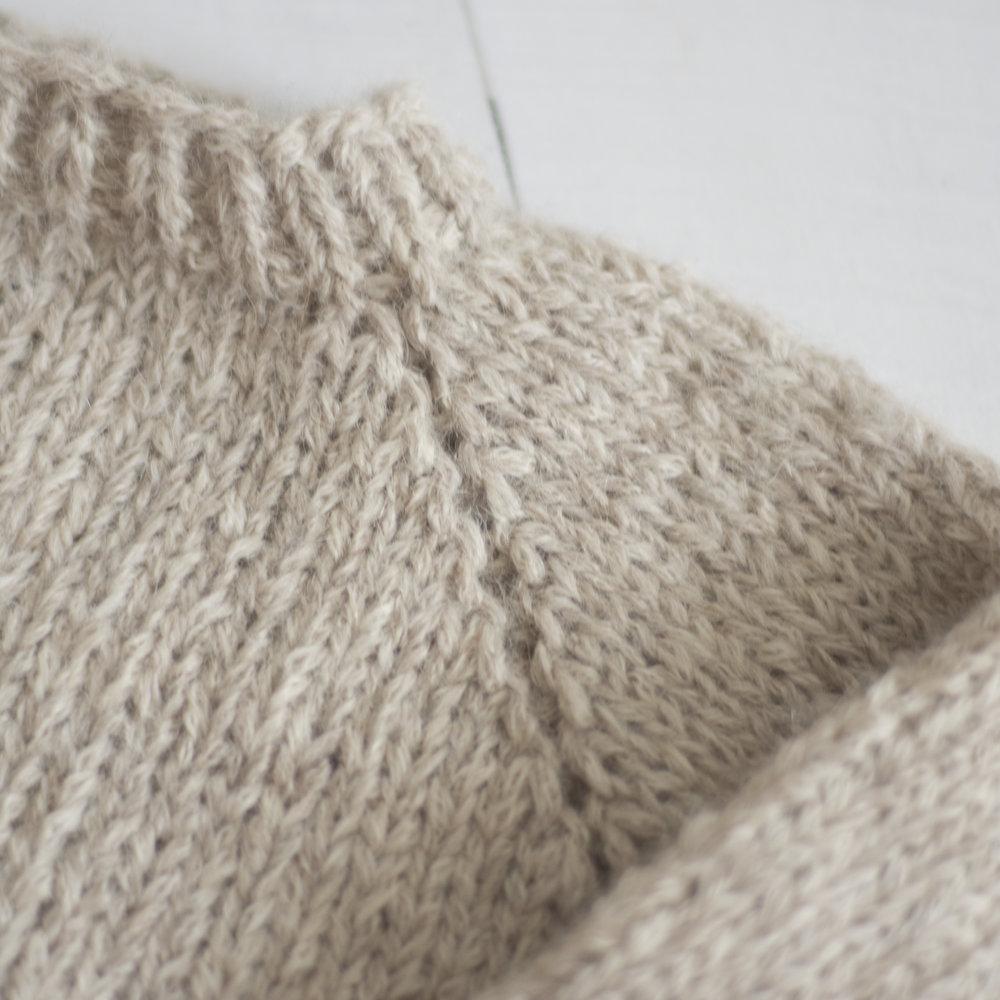 Vranggenseren  sett fra retta, her er det økt 1mv, 1 vr, 1mh. Når genseren vrenges popper den da rette masken i midten pent frem.