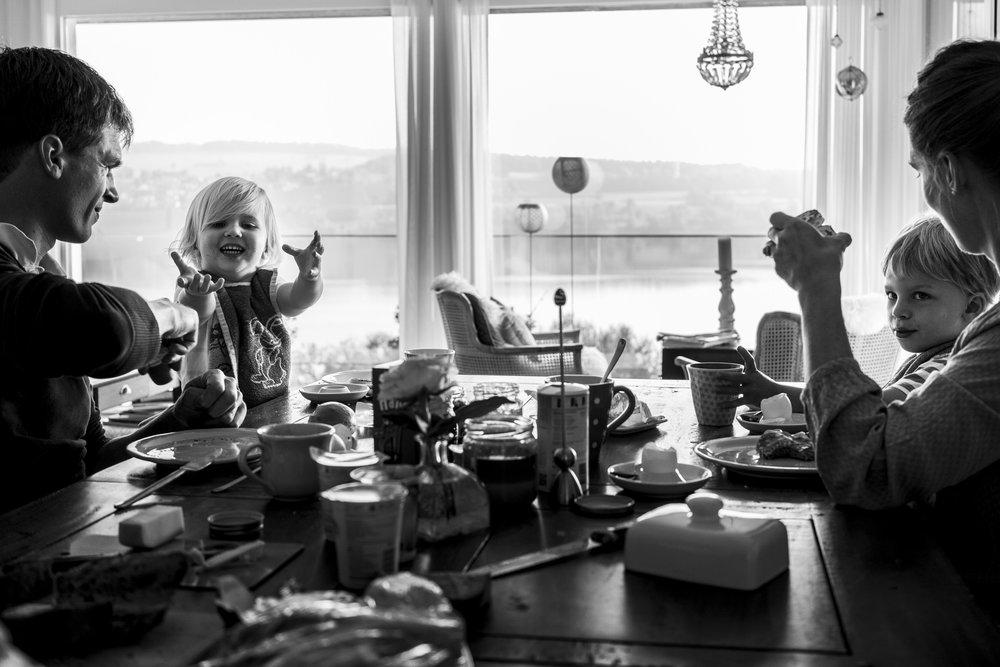 Familienfotos am See - Familie am Frühstückstisch mit See im Hintergrund