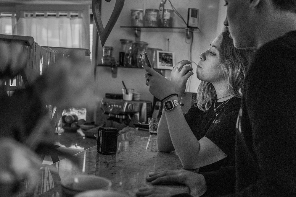 Bild aus einer Familienreportage mit älteren Kindern mit der Tochter, die Nudeln probiert und auf ihr Handy schaut