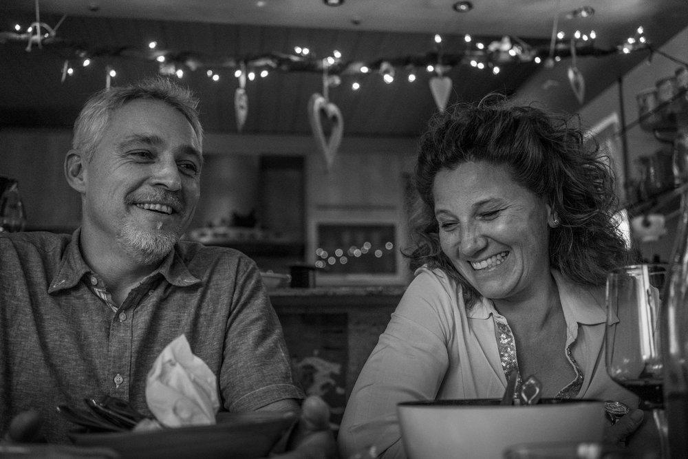 Bild aus einer Familienreportage mit älteren Kindern mit Mutter und Vater lächelnd am Tisch