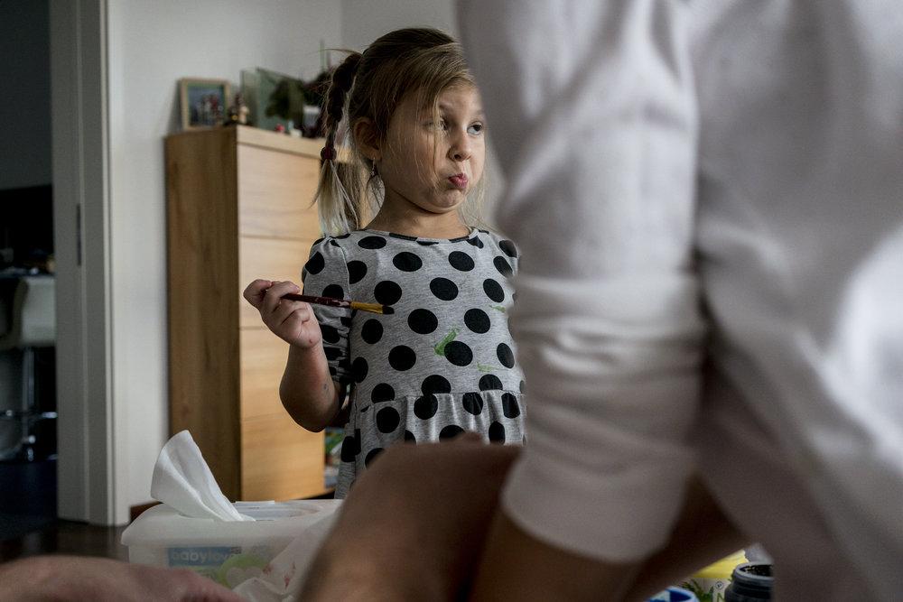 Eines meiner liebsten Familienfotos aus einem Babybauchshooting - Mädchen mit Pinsel in der Hand, bereit den Bauch der schwangeren Mama zu bemalen