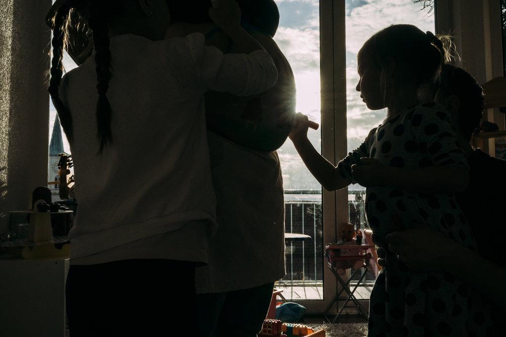 Eines meiner besten Babybauchfotos - Tochter bemalt Bauch ihrer schwangeren Mama drinnen vor dem Fenster