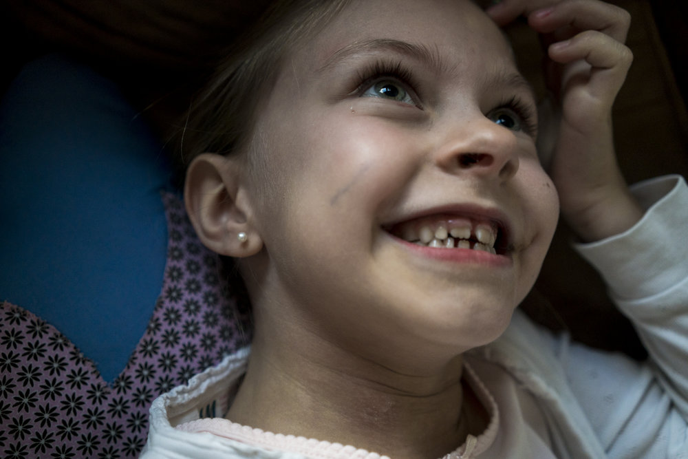 Eines meiner liebsten Familienfotos - Mädchen liegt lachend drinnen auf Sofa