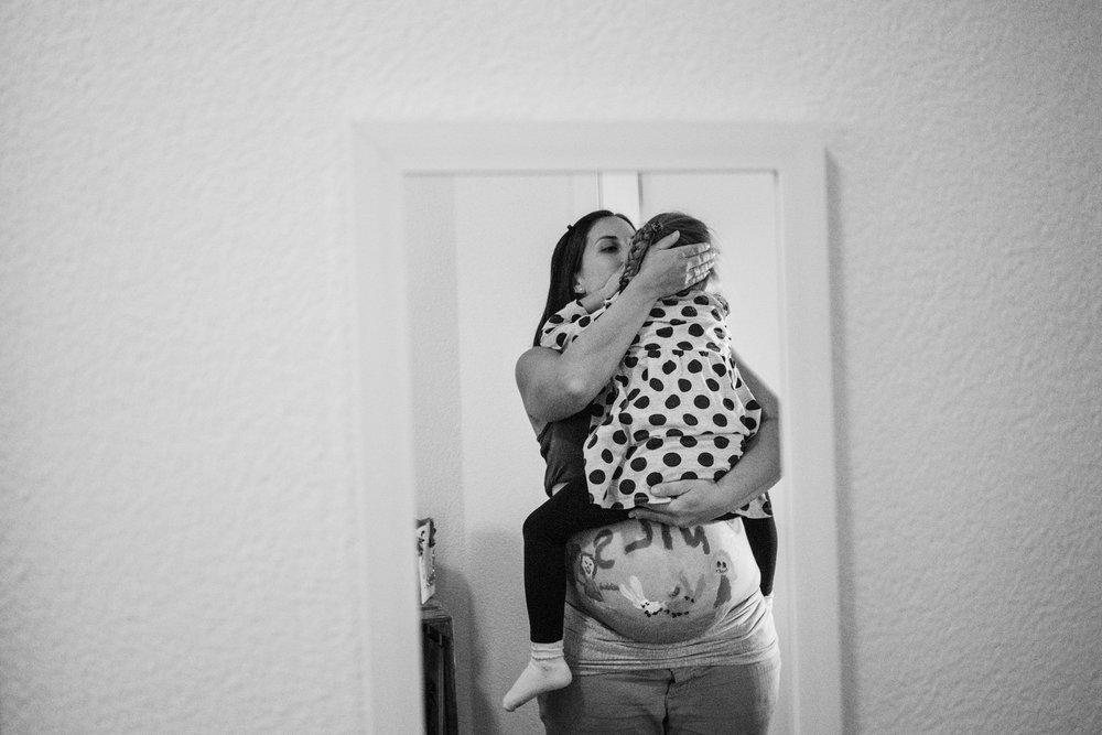 Eines meiner liebsten Babybauchfotos - schwangere Mama hat ihre Tochter auf dem Arm und tröstet sie