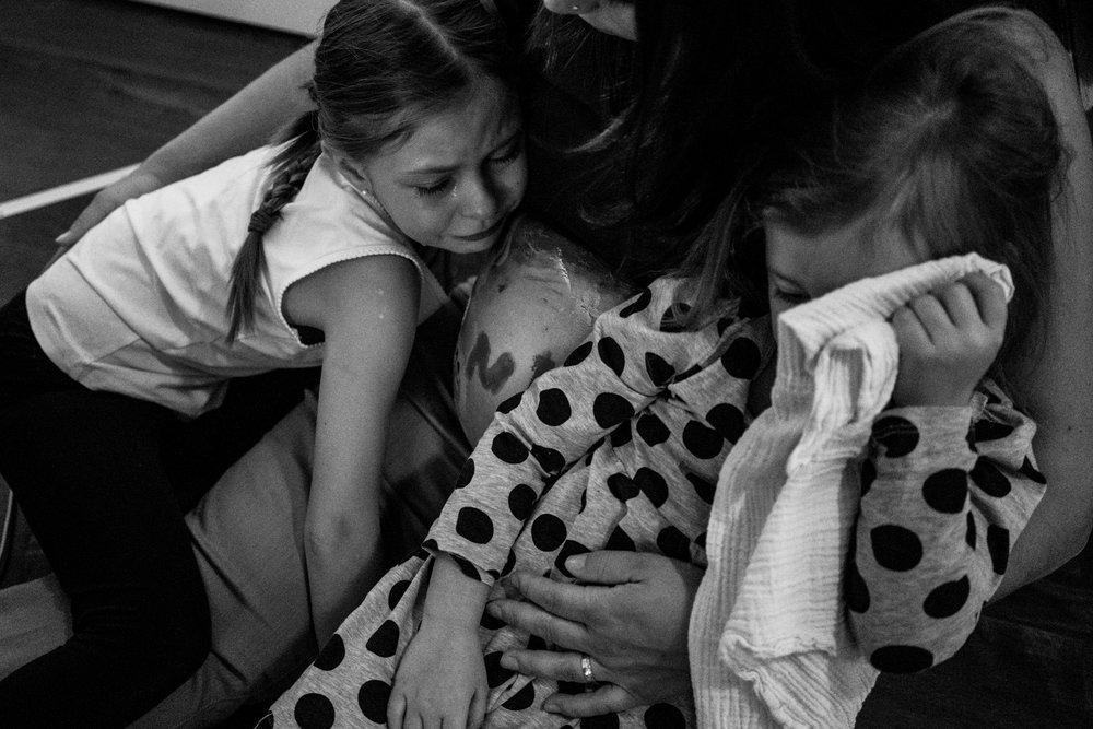 Eines meiner liebsten Babybauchfotos aus einer Familienreportage - Mama mit Babybauch tröstet ihre beiden Töchter