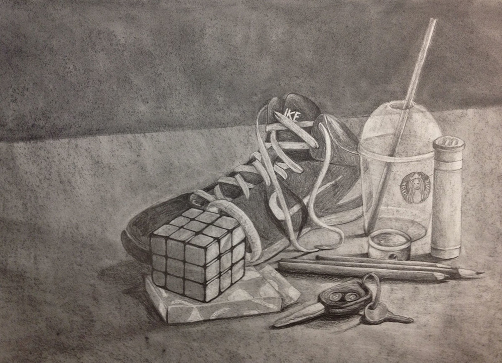 """Drawing I: Self-Portrait Still Life     (click here to view this entry on my website)     Graphite, 24x18 in. Completed as ahomework assignment to arrange and draw a still life that represents myself.   Contents: basketball sneaker, """"BE STRONG FOR HIM"""" bracelet, Rubik's cube, Hershey playing cards, car and mailbox key ring, colored pencils with sharpener, Starbucks cup, and a mini M&Ms container"""