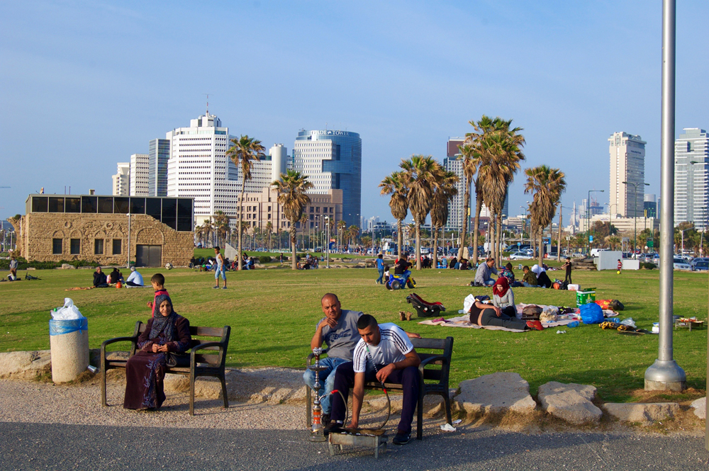 """Tel Aviv-Yafo residents use this popular waterfront park to cool off on humid summer afternoons. The former Irgun headquarters (background, left), used during the siege of Jaffa in 1948, has transitioned into a museum dedicated to the """"Liberators of Jaffa."""" This park is the approximate spot where the Bashar Masalha was shot and killed by a police officer on March 8th."""