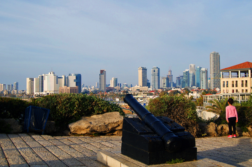 A girl overlooks the city of Tel Aviv from the hill of Old Jaffa. The cast-iron canon in the foreground was brought to the Ottoman governor's palace to protect the port from pirates and Bedouin raiders in the 18th century. It sits on the same site that was defended by Arab and British forces during Israel's War for Independence in 1948.