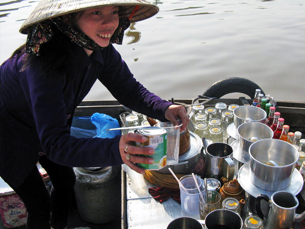 A young woman happily brewing hot ca phe for her unexpected river guests.