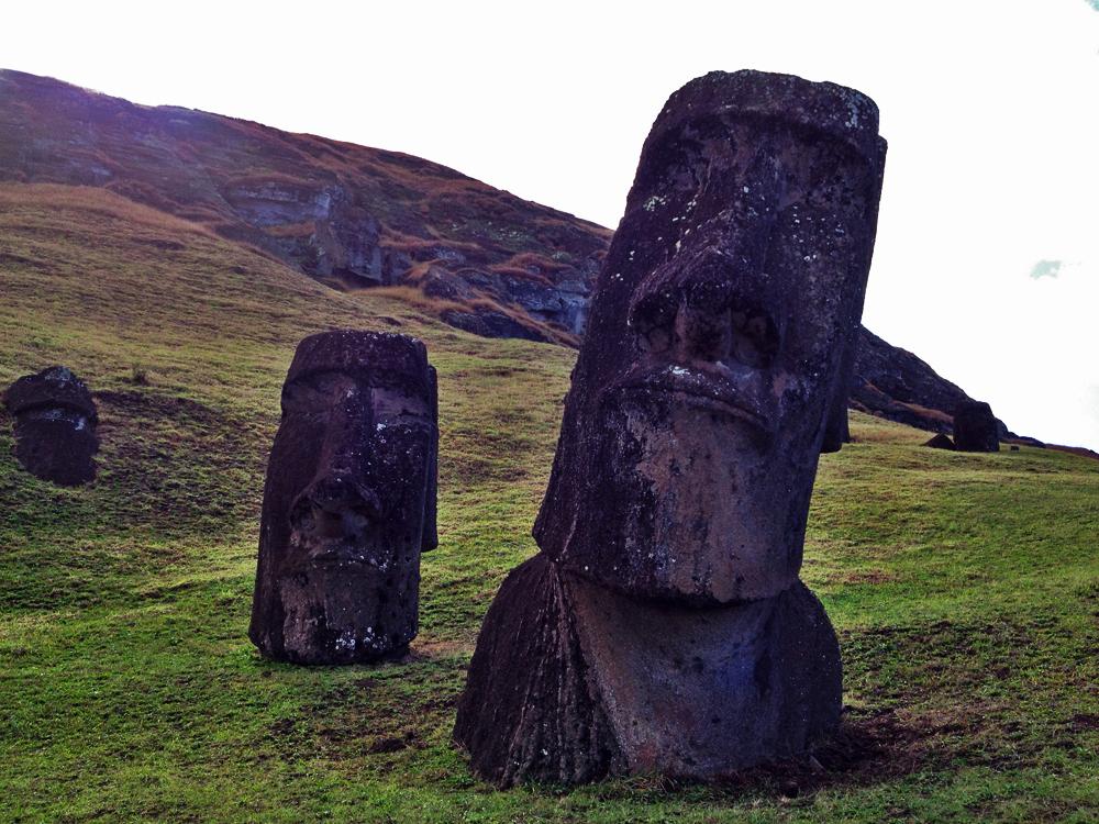 Half-buried moai erupting from the volcanic quarry Rano Raraku