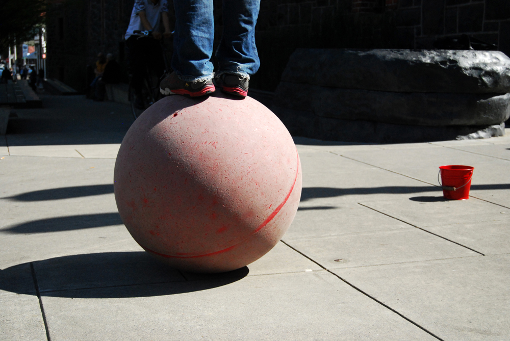 A street artist performs in the Pearl District of Portland, OR, USA. I found him balancing on the ball while juggling his signature move.