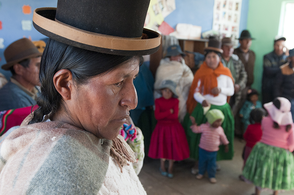 One of the Calamarca weavers, wearing a characteristic bowler hat, listens to the presentations made by her colleagues during a visit by Save the Children
