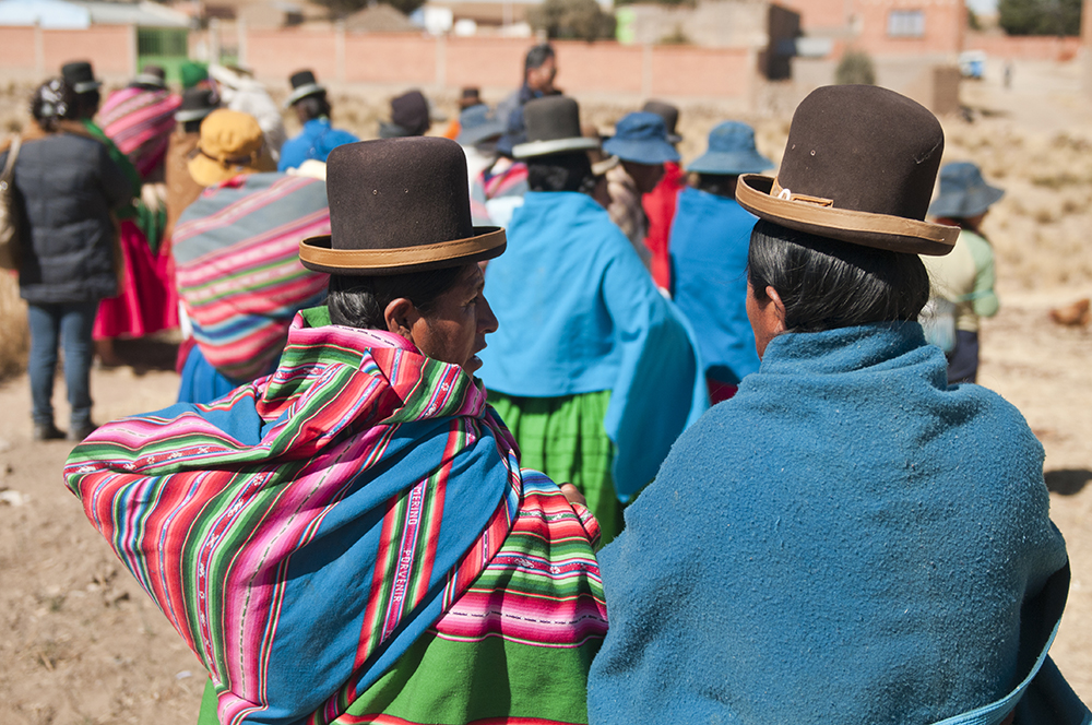 Two Aymaran women watch their neighbors prepare freeze dried potatoes