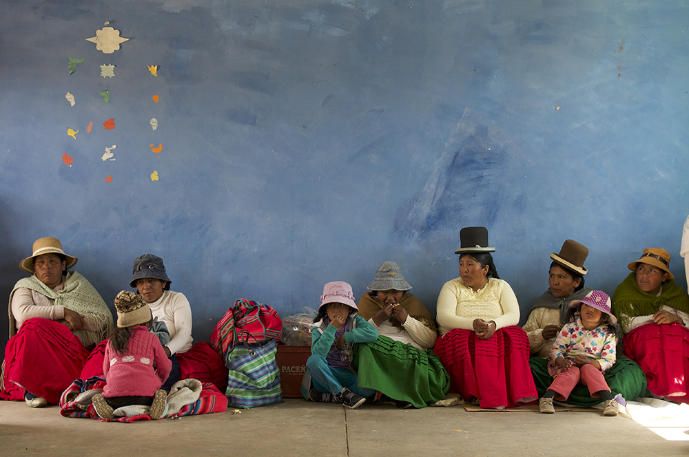 Members of the Calamarca Weavers Association listen to speeches during the Save the Children visit.