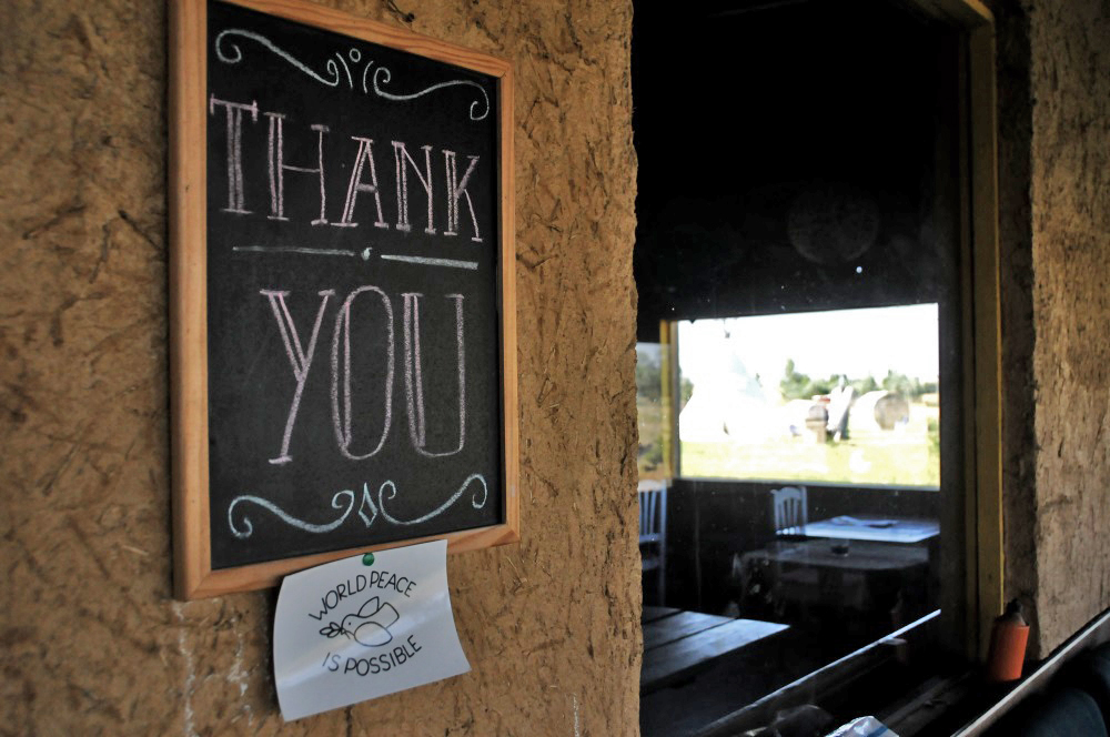 A sign at an albergue reads 'THANK YOU' and under it a smaller sign reading 'World Peace is Possible.'