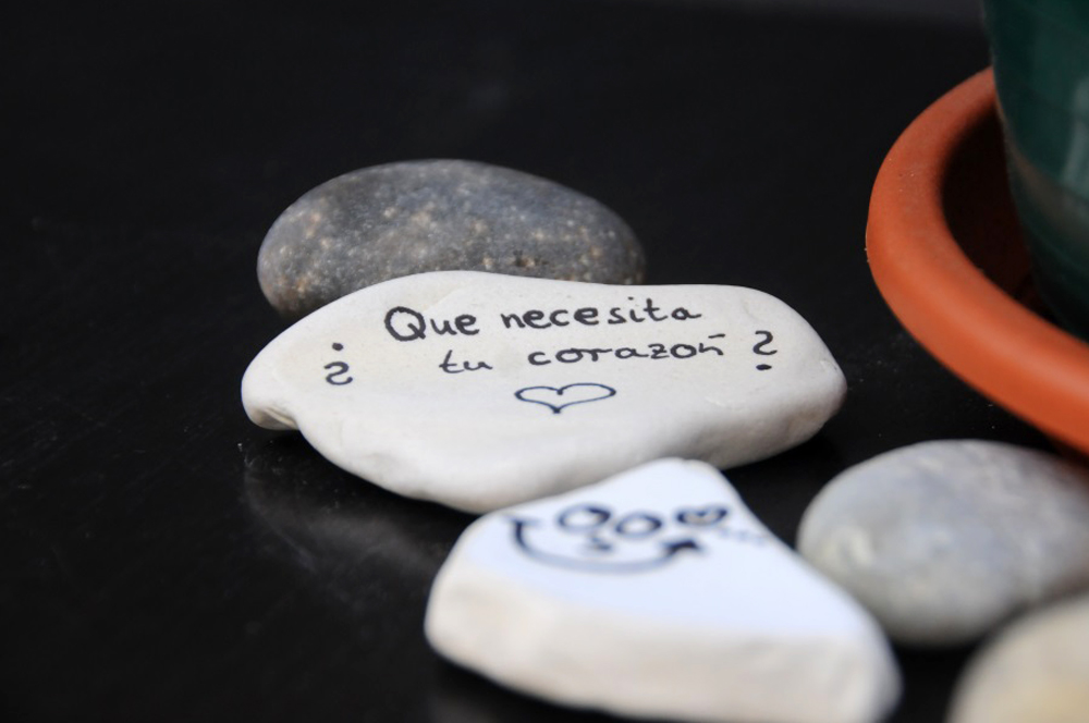 "A rock displays the message ""Que necesita tu corazon?"" (What does your heart need?)"