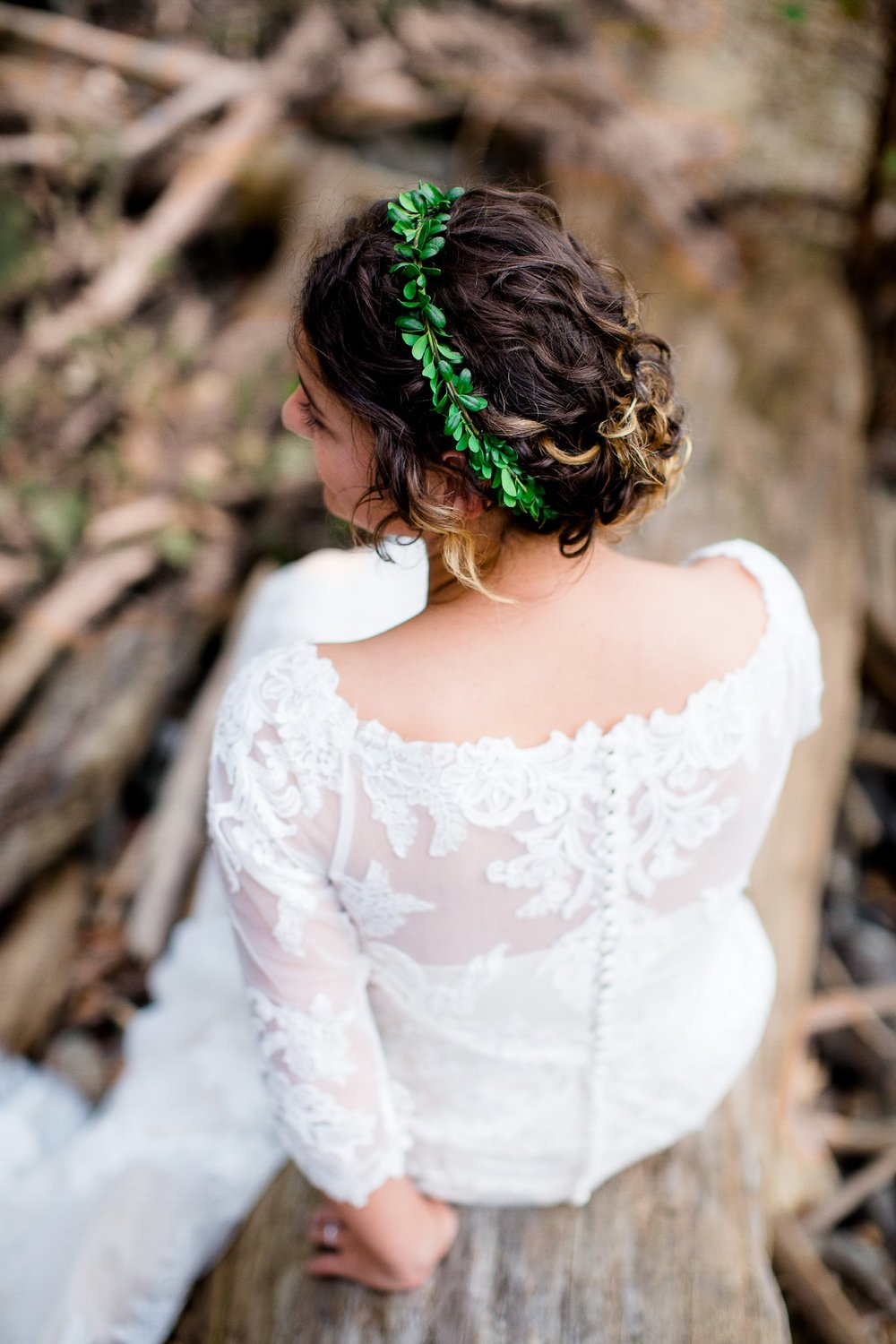 bride in lace dress with her back to the camera with a green garland in her hair