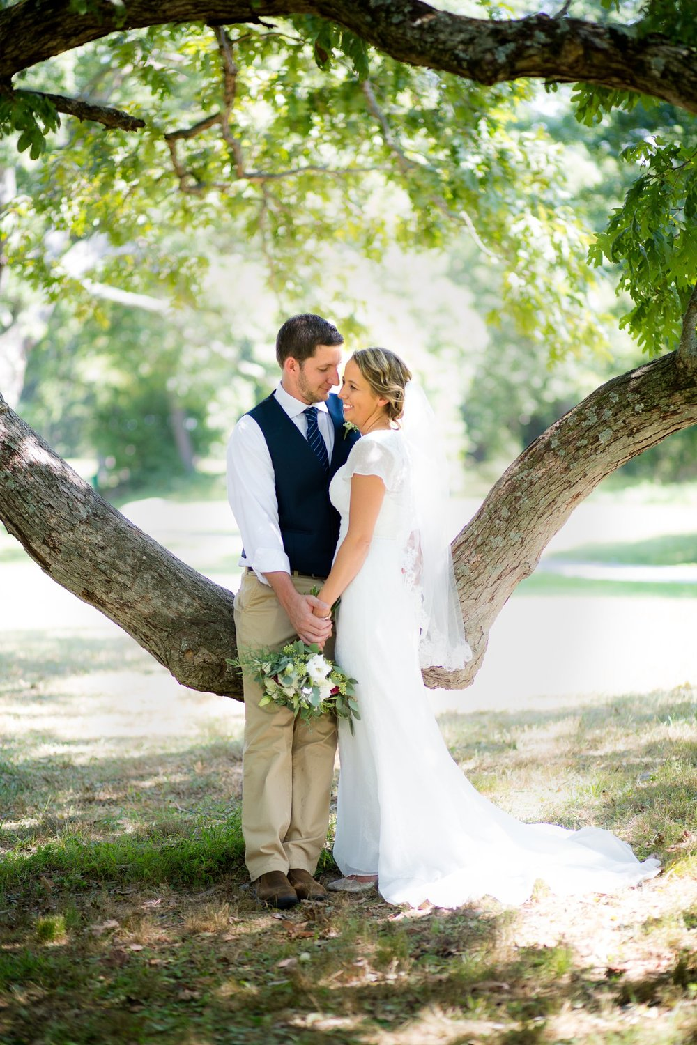 elegantly styled bride and groom smiling and standing by a large tree